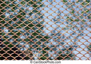 Rusty fence above blue sky - Chain link rusty fence on a...