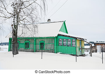 a photograph of a house under the snow during the cold winter
