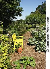 Vegetable Garden - A yellow bench in a vegetable garden.
