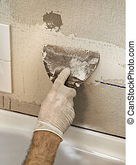 Wall Tiling with trowel - Closeup of a mans hand applying...