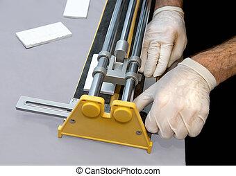 Man Using Tile Cutter - Closeup view of man's hands...