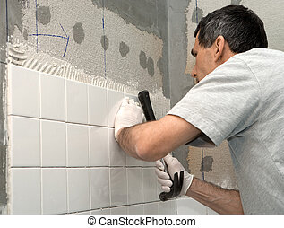Man Tiling A Wall - Man setting tile on cement board He is...