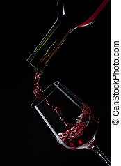 red wine pouring into wine glass isolated on black