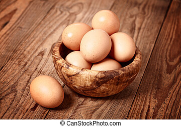 fresh brown eggs on wooden background