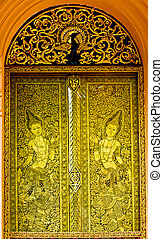 Gold carved ancient door of temple Thailand.