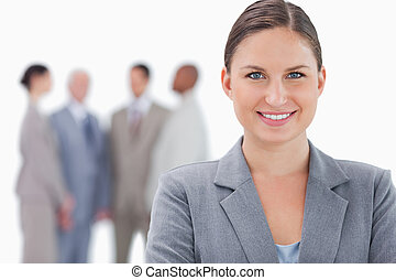 Smiling businesswoman with colleagues behind her