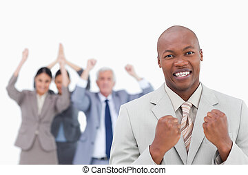 Successful businessman with cheering team behind him