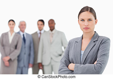 Serious tradeswoman with arms folded and colleagues behind her