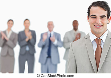 Businessman with applauding colleagues behind him