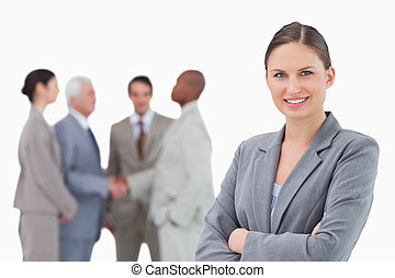Smiling saleswoman with folded arms and colleagues behind her