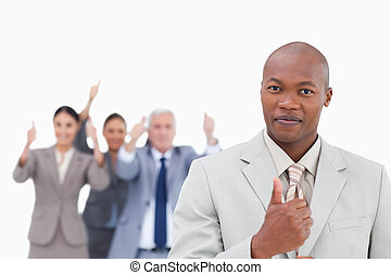 Businessman with cheering team behind him giving thumb up