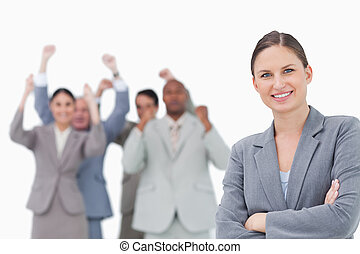Smiling businesswoman with cheering team behind her