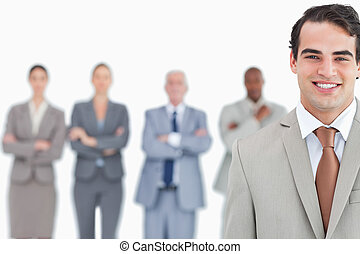 Smiling salesman with his team behind him