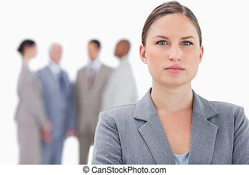 Serious businesswoman with co-workers behind her against a...