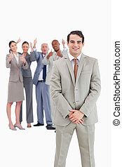 Smiling businessman with cheering team behind him