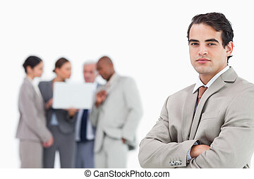 Businessman with arms folded and team behind him