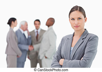 Serious saleswoman with arms folded and colleagues behind her