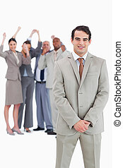 Businessman with cheering team behind him