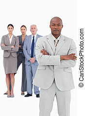 Businessman with folded arms and team behind him