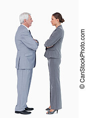 Business partner standing face to face with arms folded