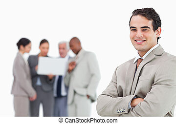Smiling salesman with arms folded and colleagues behind him...