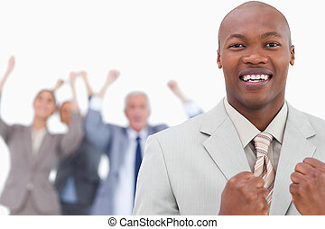 Triumphant businessman with cheering team behind him
