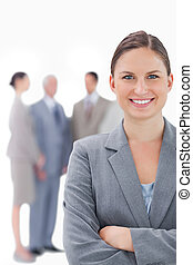 Smiling businesswoman with her colleagues behind her