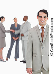 Smiling tradesman with businesspeople behind him
