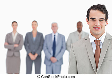 Smiling businessman with his team behind him
