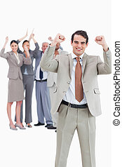 Cheering businessman with team behind him against a white...