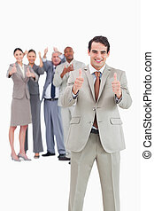 Smiling businessman with team behind him giving thumbs up