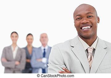 Smiling salesman with team behind him