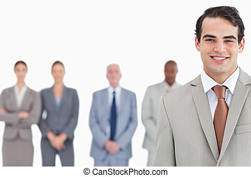 Smiling salesman with colleagues behind him
