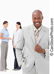 Smiling tradesman with associates behind him