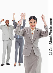 Triumphant saleswoman with cheering associates behind her