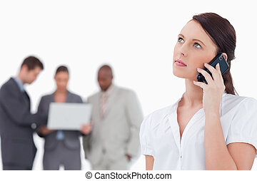 Businesswoman listening to caller with colleagues behind her...