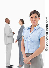 Saleswoman with talking associates behind her against a...