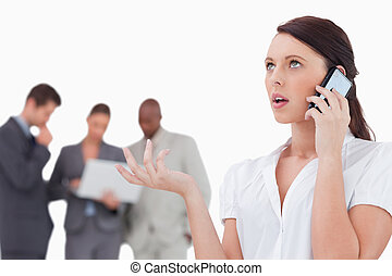 Saleswoman talking on the phone with colleagues behind her