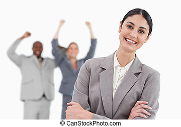 Smiling businesswoman with cheering associates behind her