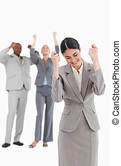 Successful businesswoman with cheering associates behind her