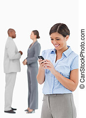 Businesswoman looking at cellphone with associates behind her
