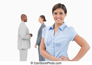 Smiling tradeswoman with talking associates behind her