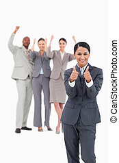 Saleswoman with cheering team behind her giving thumbs up