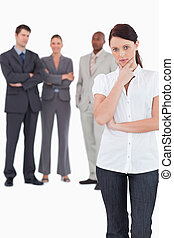 Thinking businesswoman with three colleagues behind her