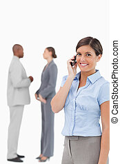 Smiling saleswoman on the phone with associates behind her