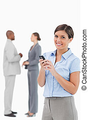 Smiling tradeswoman with cellphone and associates behind her