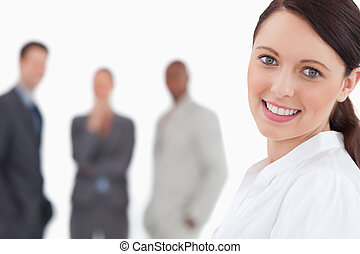 Smiling businesswoman with three colleagues behind her