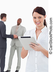 Businesswoman with tablet and associates behind her