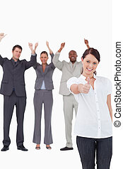 Businesswoman with cheering colleagues behind her giving approval