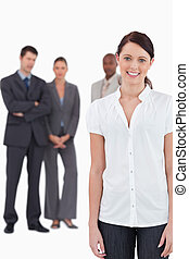 Smiling businesswoman with three co-workers behind her